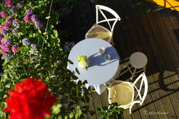 Ein Tasse Kaffee auf der Terrasse, umgeben von Blumen und Sonnenlicht.